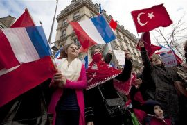 Franco-Turkish demonstrators wave French and Turkish flags near the French Senate in Paris
